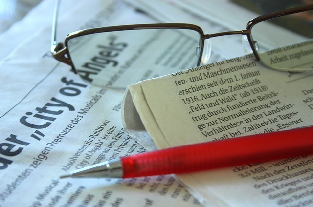 Red pen and spectacles on newspaper to signify Selling Articles