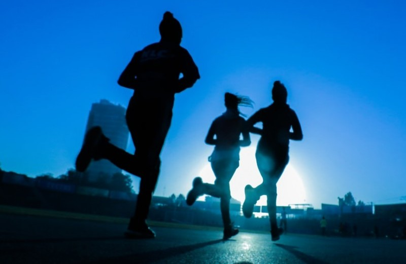 Three figures in silhouette exercising through jogging to signify make money fast at home exercising and losing weight