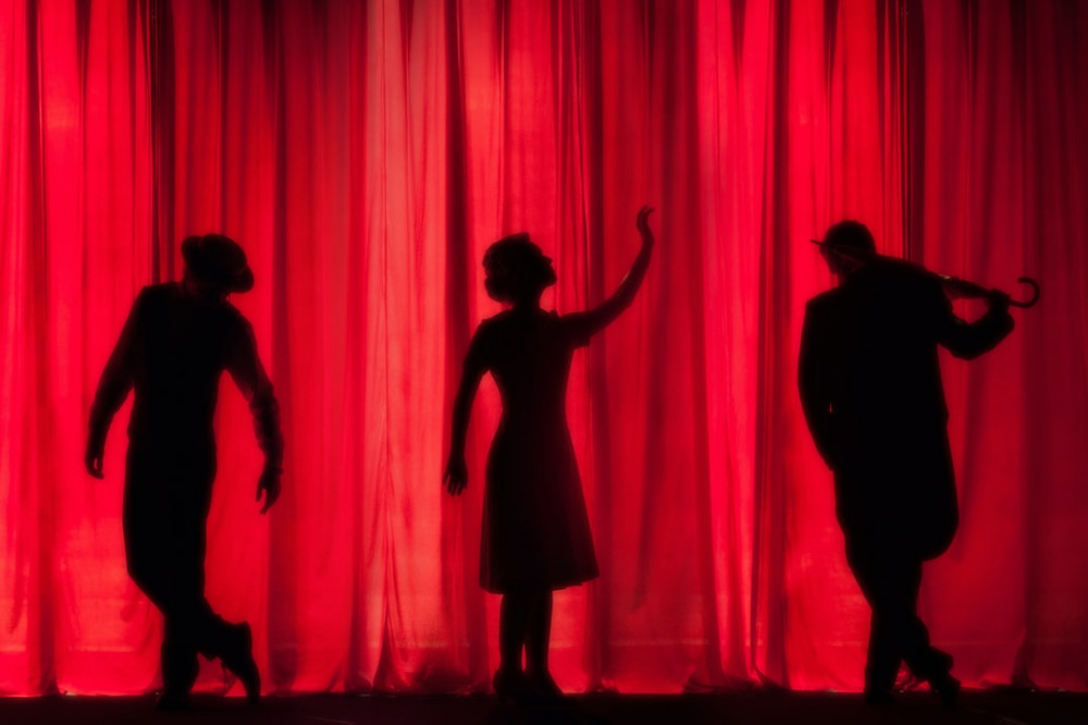 Solhoutted bodies performing in theater with red light against curtain