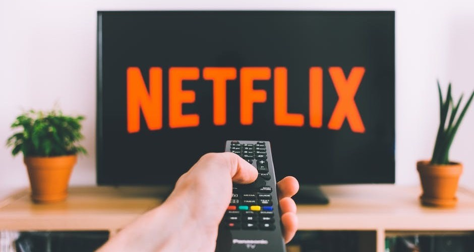A hand holding a remotecontrol to control netflix to say get paid for your screen time