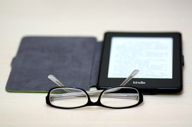 An open kindle book with spectacles before it