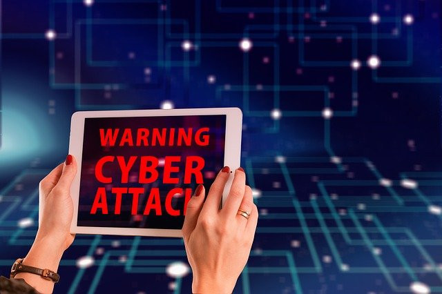 WARNING CYBER ATTACK written in red on an iPad in front of a blue electronic background