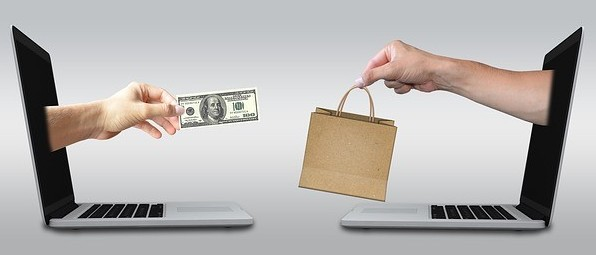 2 hands projecting out of 2 laptop screens, one handing out a dollar bill and another a shopping bag to signify Summary of All About Keywords – Part III: Understanding keywords and how to use them for selling