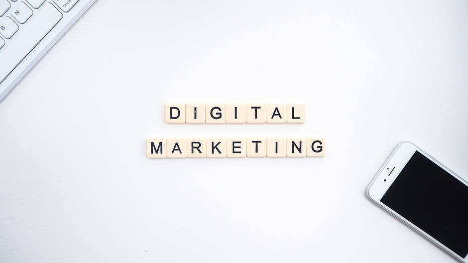 The words 'DIGITAL MARKETING' written on a white background where one can see a keyboard and an iPhone for internet marketing
