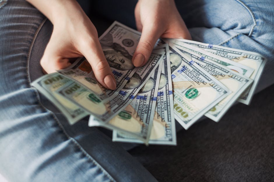 Lady's hands holding spread out 100 dollar bills to signify The three most common MLM payment structures: Unilevel, Breakaway and Binary