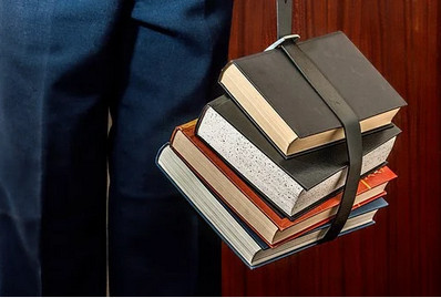 Studentwith load of books tied in belt to signify academic decisions