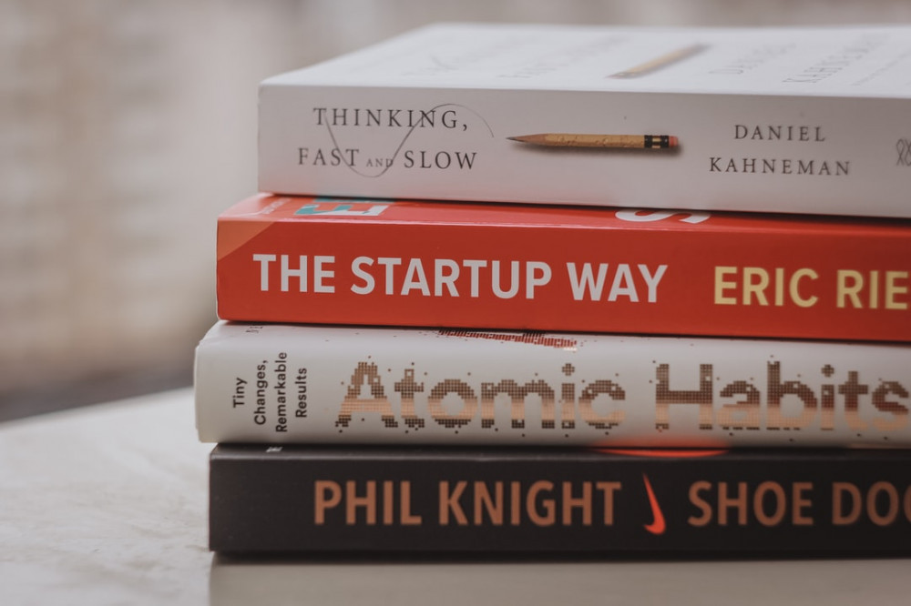 Pile of 4 large books, one with title: The Startup Way