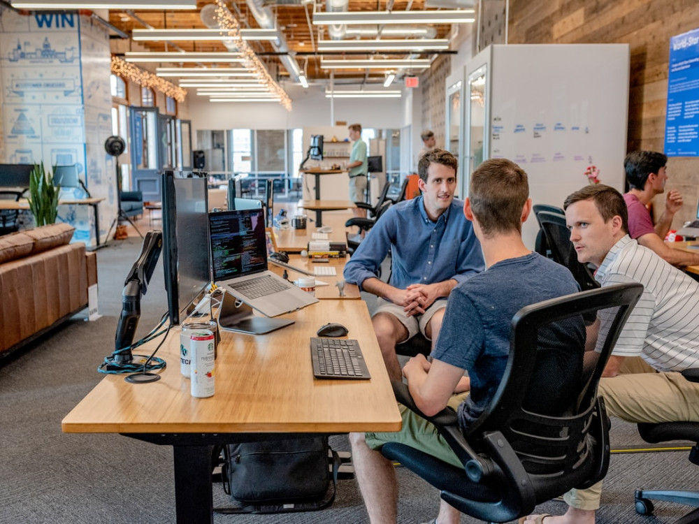 3 men discussing in a large open office