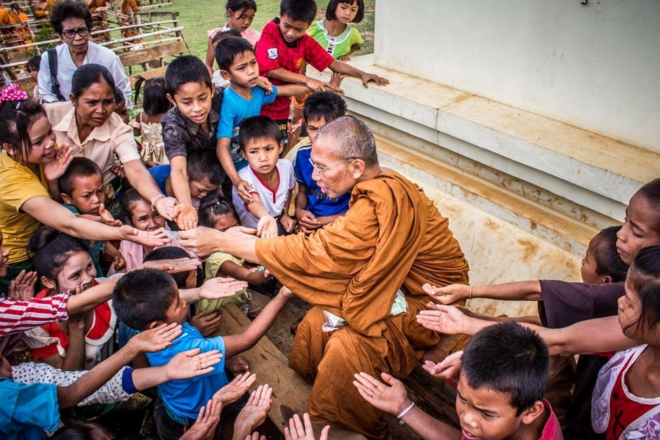 Buddhist monk distributing food to children to signify Work as a Charity Collector to earn fast money
