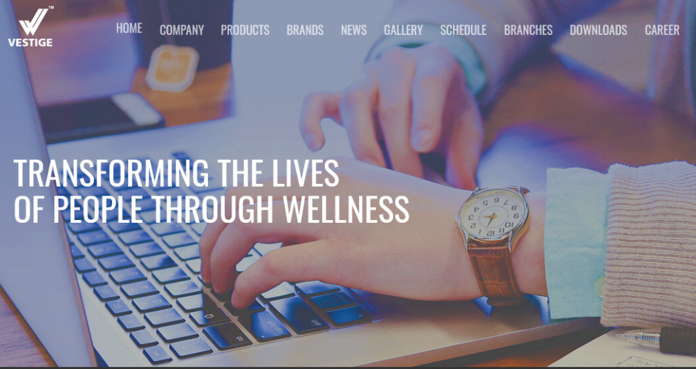 Vestige Marketing image of a female hand typing on a laptop showing the words 'Transforming the lives of people through wellness' to signify DXN Global versus Vestige Marketing