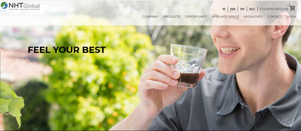 NHT Global official website homepage showing a smiling man drinking brownish liquid from a glass and beside him the words 'Feel your best'
