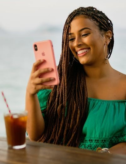Smiling lady consulting her phone to say Get Paid From your iPhone (smartphone)