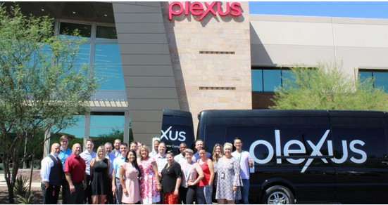 Plexus headquarters building with people lined up before it and a blue-black plexus bus