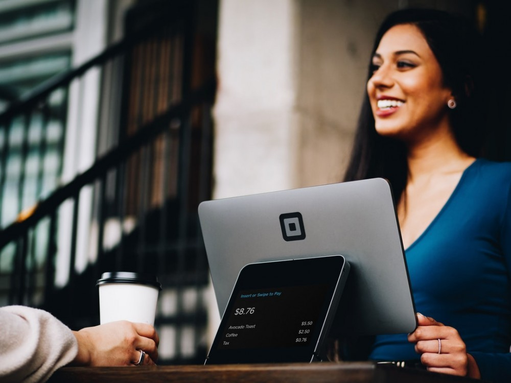 Smiling lady before a laptop talking to a customer as a customer service representative