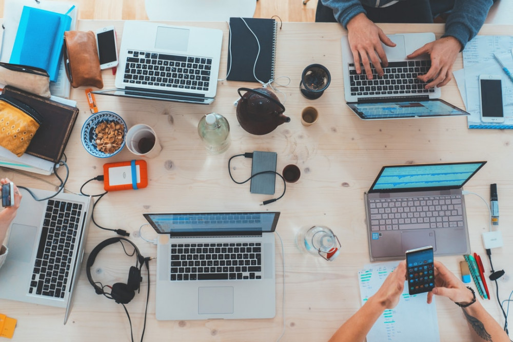Laptops, mobile phones, headphones, and other devices on a meetng table to signify 5 Reasons NOT To Have a Marketing Strategy – And some Suggestions