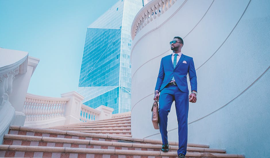 Young man in blue suit with a briefcase standing among skyscrapers to signify Benefits of Affiliate Programs for Affiliate Marketers