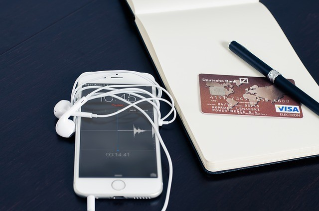 A smartphone with earphones, a VISA credit card and a pen lying on a book to signigy pay with a phone
