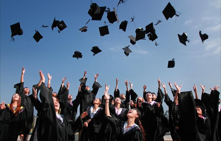 Graduates throwing their caps into the sky for comparison between the cost of WEalthy Affiliate education and college one