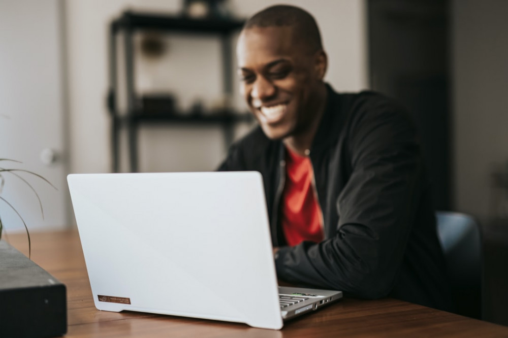 Smiling man in front of a white laptop