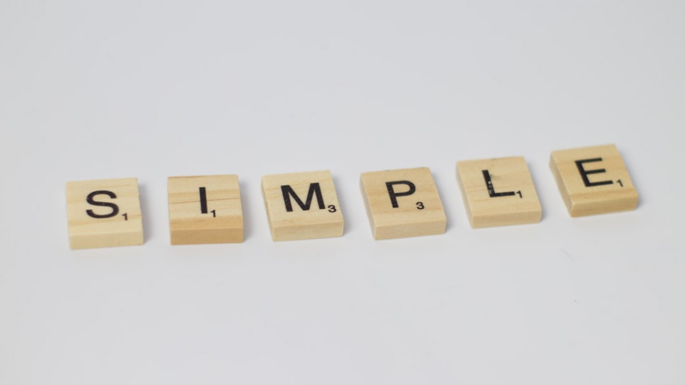 SIMPLE written on individual wooden cubes against ash background