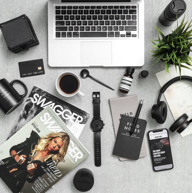 Laptop keyboard, magazines, headphone, iphone and other objects lying on a table to signify All You Need To Know To Become a Very Successful Affiliate Marketer