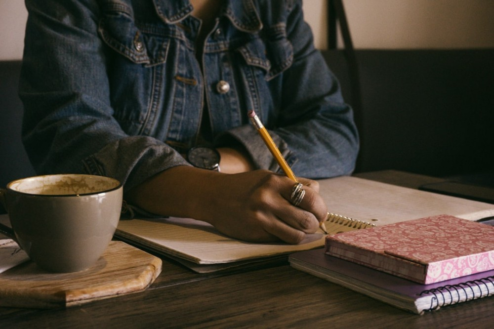 Woman writing in a notebook with a pencil to signify become a writer for 88 Ways for Making Money Online at Home Free (Part VIII)