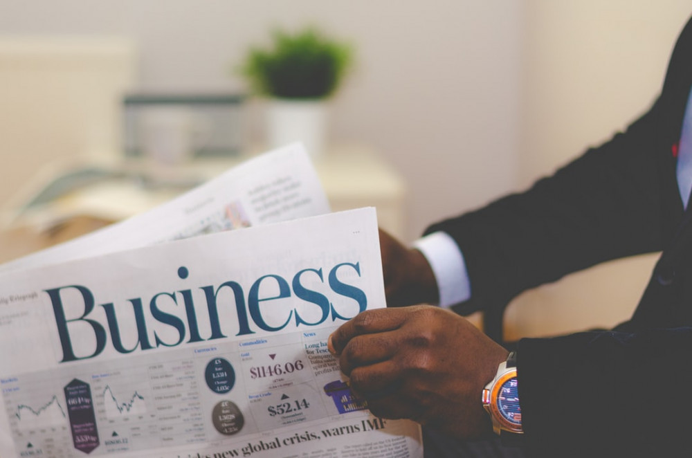 Hands holdinga Businessnewspaper for What Are You Doing to Create a Thriving Business?