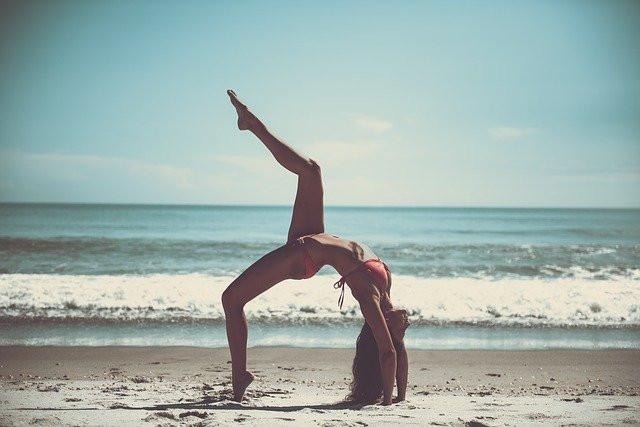 a slim woman doing yoga on the beach