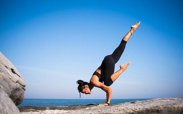a woman doing yoga near sea