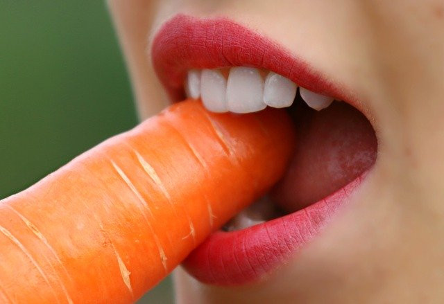 a woman eating a carrot