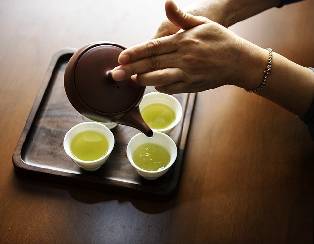 Pouring green tea into cups