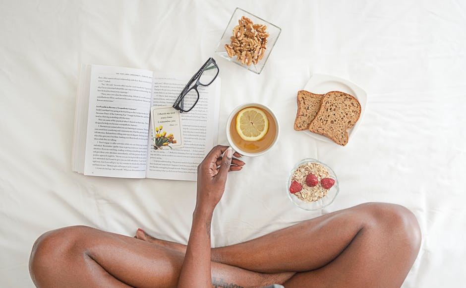 legs of a woman, a book and food
