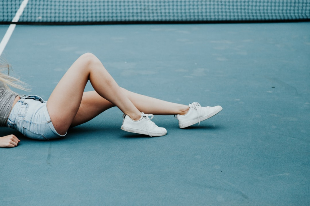a woman's legs on the tennis court
