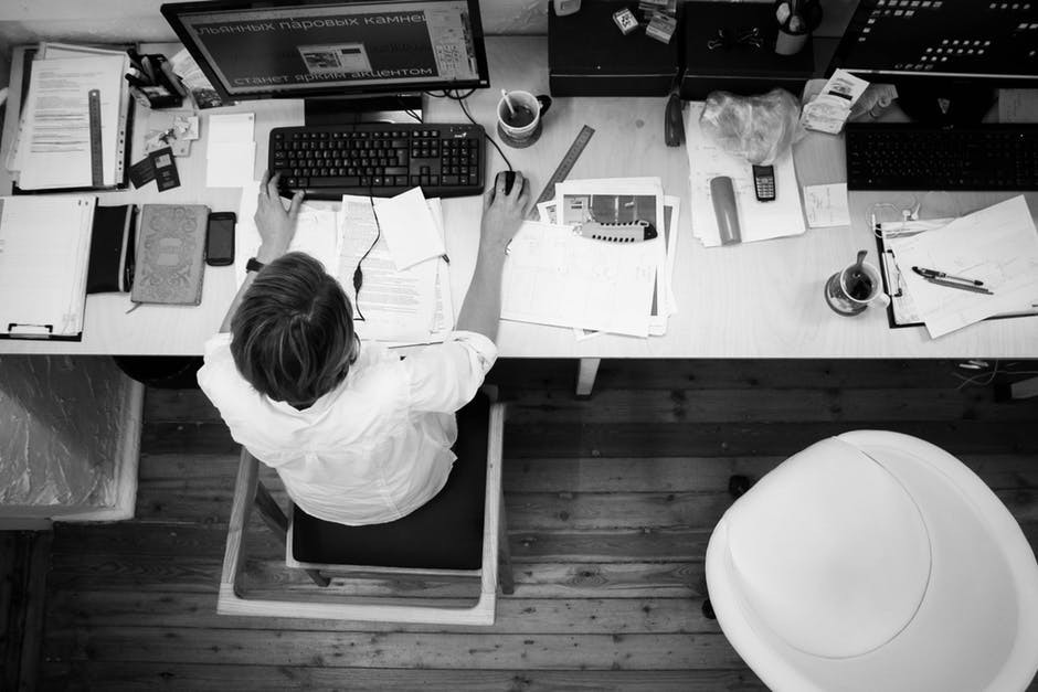 Man sitting at a desk, in need of lower back stretches at work