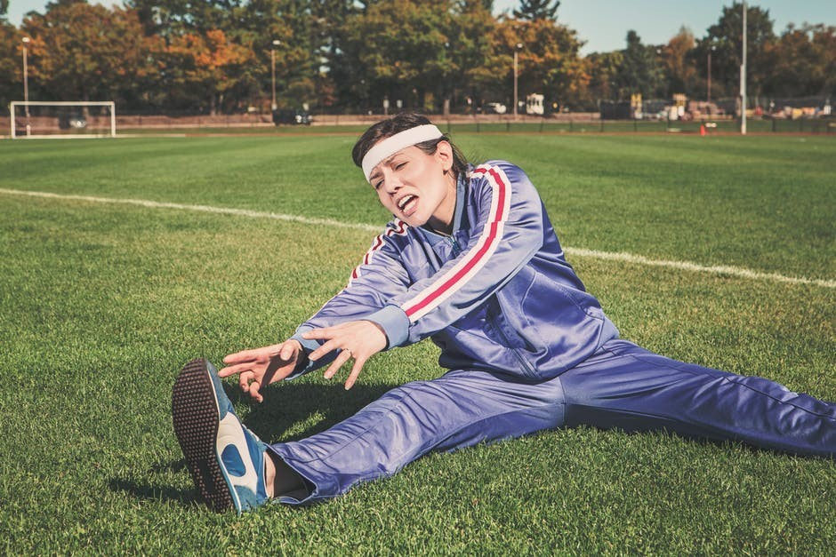 Person on grass performing stretching exercises for lower back pain