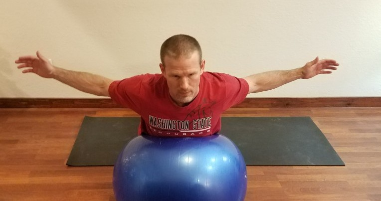 Back extension on a ball, demonstrating exercises that help posture