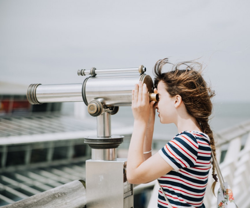 a young lady looking through a telescope