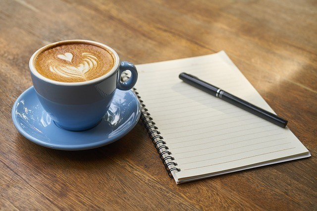 Blue cup of coffee next to an open journal and pen