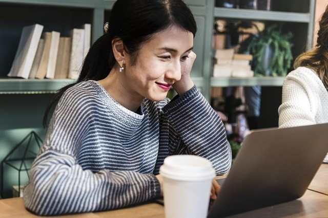 Asian woman working at computer with coffee