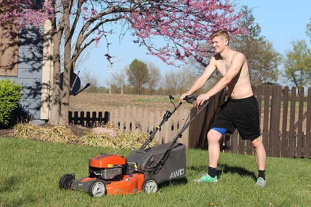 Young guy mowing yard in the spring