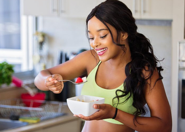 healthy female eating with bowl and spoon