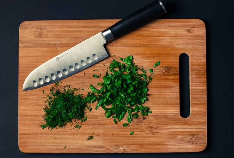 cutting board with knife and chopped up herbs