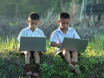 Two Boys Working Side by Side on Laptops