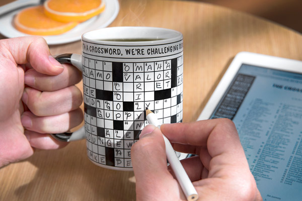 Man tackling a crossword puzzle on the surface of his coffee mug.