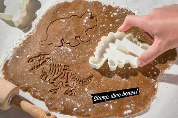 Man stamping out Dinosaur-shaped cookies.