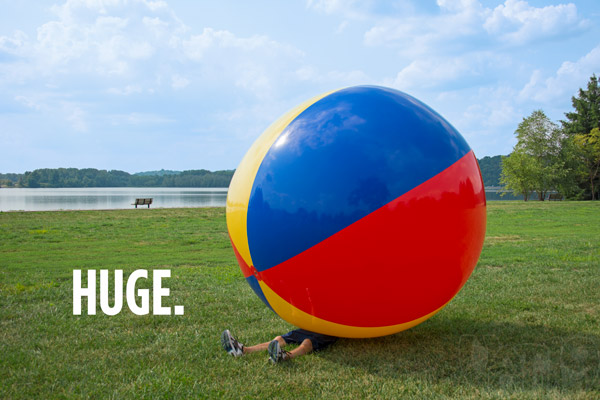 Man underneath an enormous 9-foot beach ball.