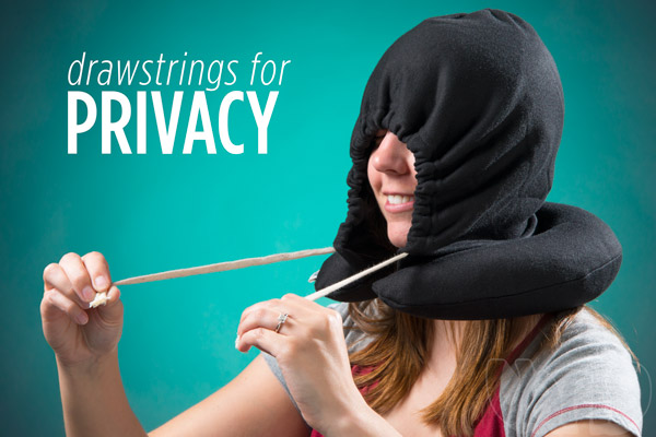 Woman pulls the drawstrings on a Hoodie Pillow for privacy.