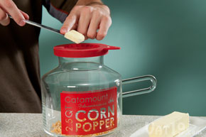 Add the desired amount of butter to the popcorn popper's melting lid.