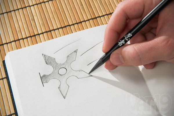 Man using a Ninja Pencil to draw a throwing star.