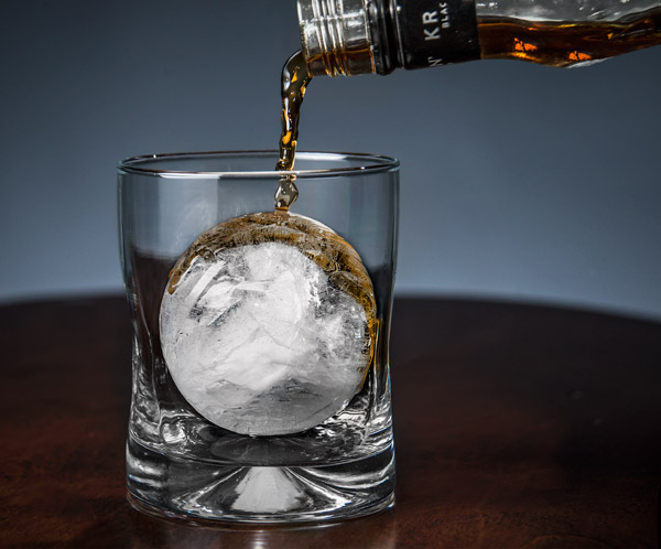 Pouring whiskey onto a large ice ball.
